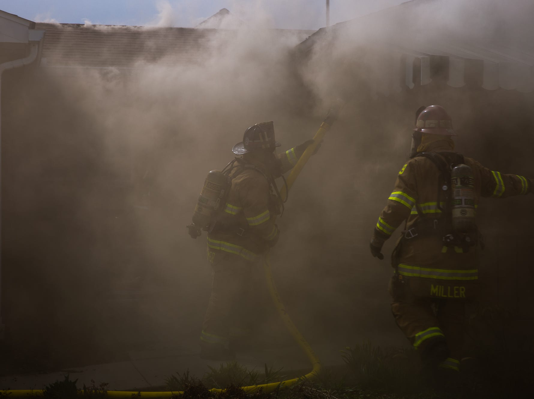Volunteer firefighter Brady Cromer and Captain Geoff Miller gear up to begin the initial interior attack at the scene of a house fire on the 100 block of Mumma Ave., Saturday, March 30, 2019, in Penn Township. No one was injured in the fire, which appears to have been an accidental fire in the kitchen, said Hanover Area Fire & Rescue Chief Tony Clousher.
