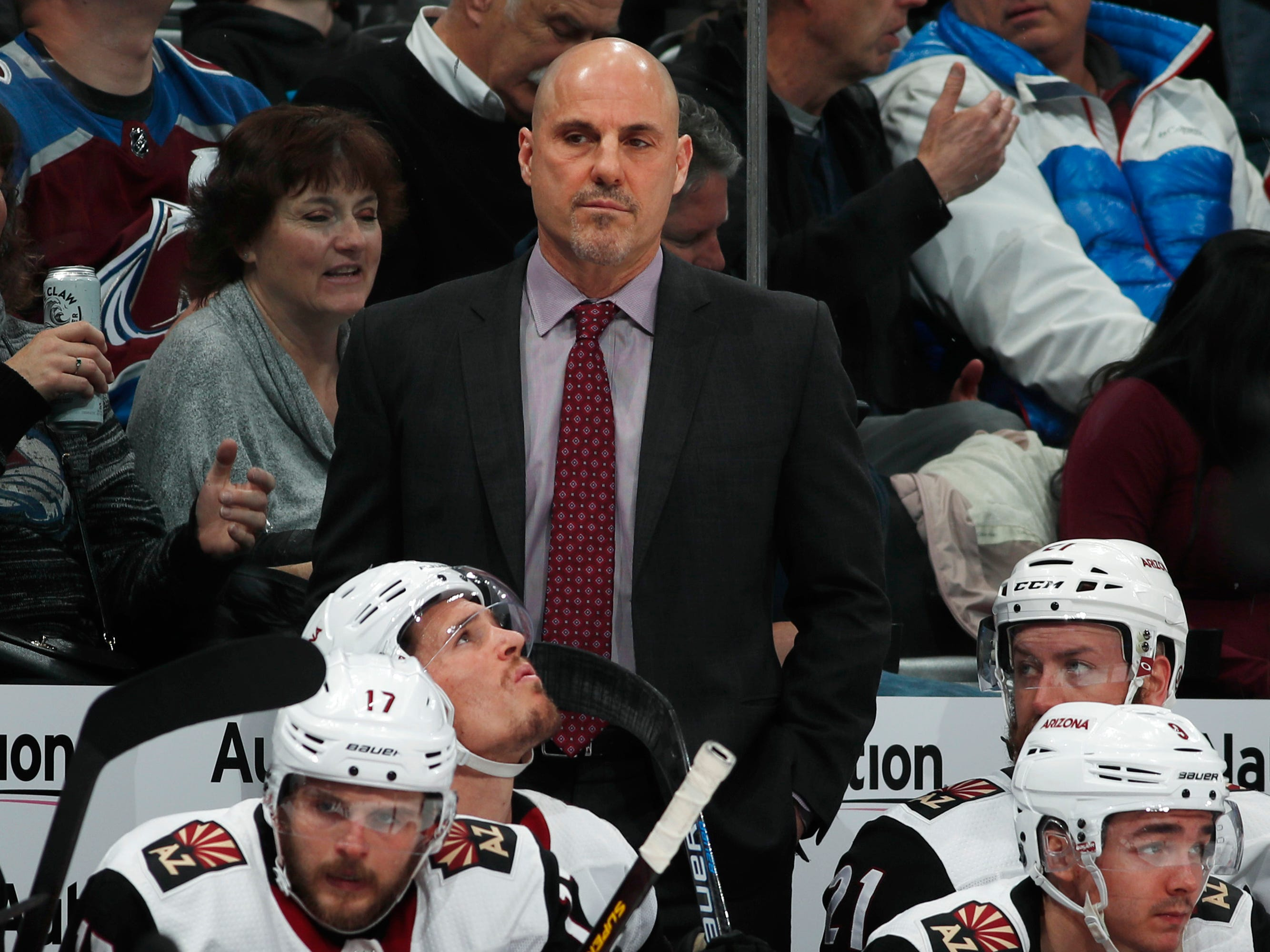 Arizona Coyotes head coach Rick Tocchet, center top, looks on in the second period of an NHL hockey game  against the Colorado Avalanche, Friday, March 29, 2019, in Denver.