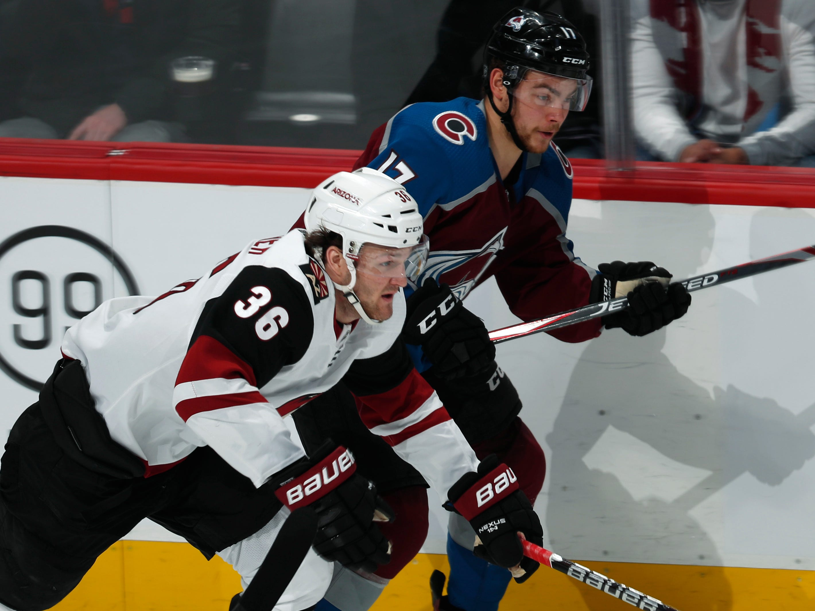 Arizona Coyotes right wing Christian Fischer, front, pursues the puck with Colorado Avalanche center Tyson Jost in the first period of an NHL hockey game Friday, March 29, 2019, in Denver.