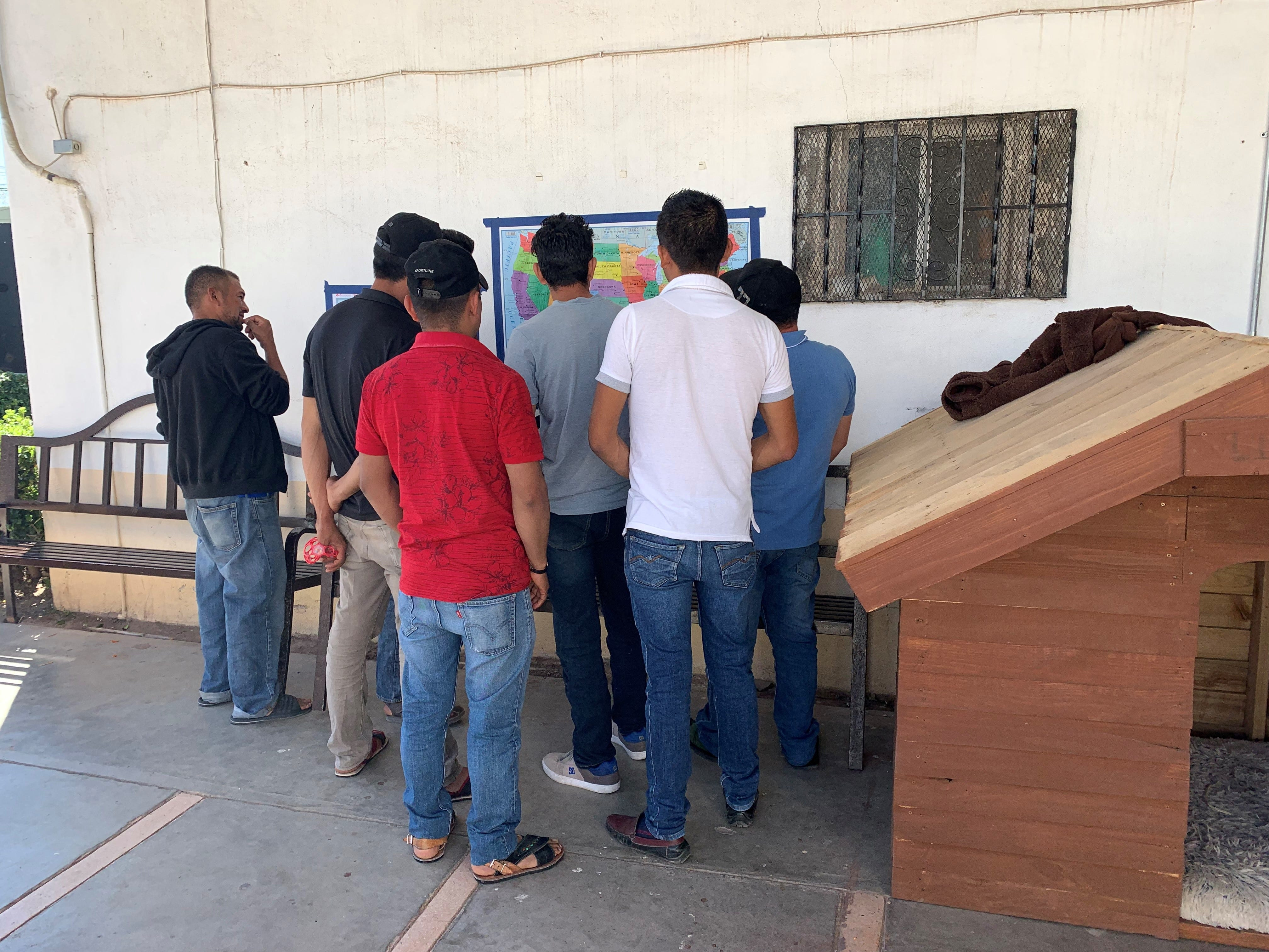 A group of migrant men look at the map of the U.S. placed inside the CAME shelter in Agua Prieta, Sonora, on March 28, 2019.