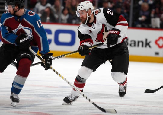 Arizona Coyotes center Derek Stepan, right, passes the puck past Colorado Avalanche center Alexander Kerfoot in the second period of an NHL hockey game Friday, March 29, 2019, in Denver.