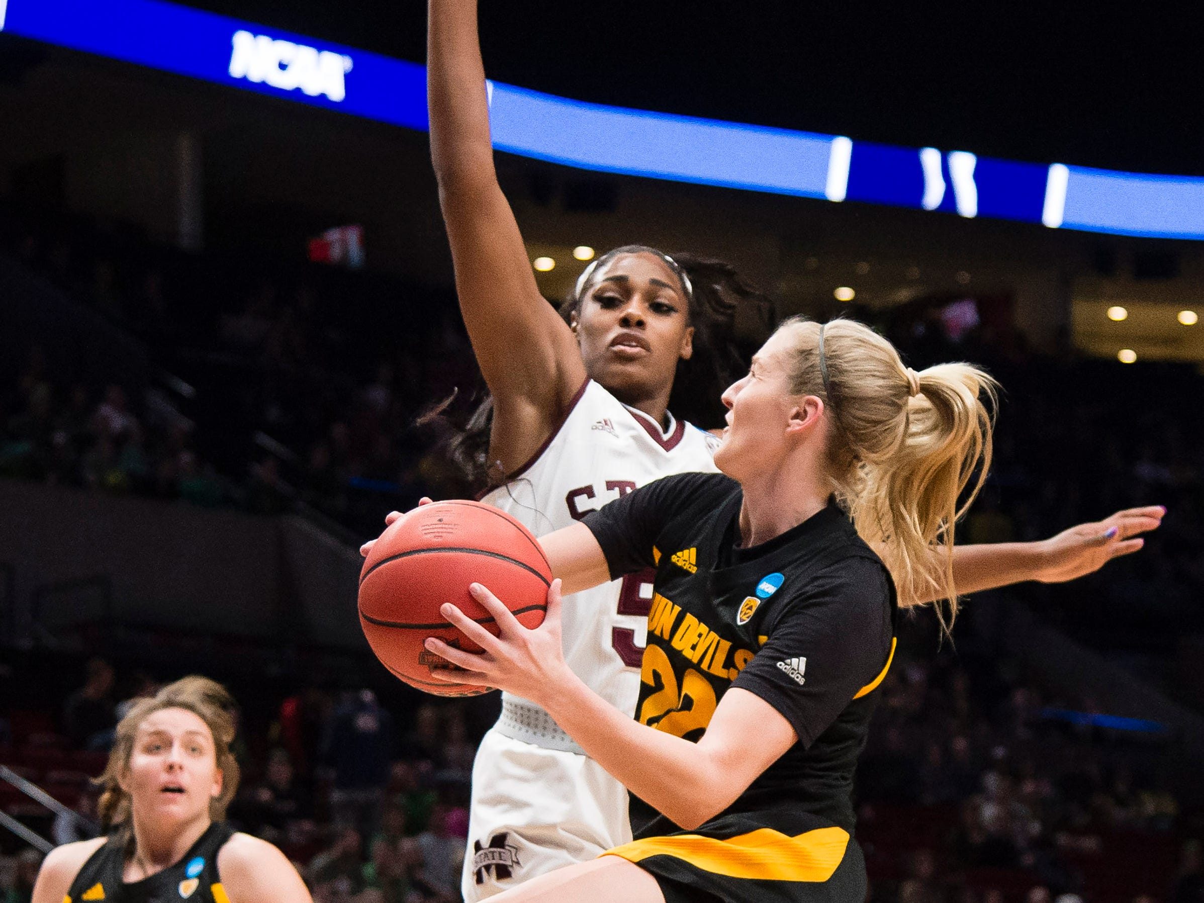 Mar 29, 2019; Portland, OR, USA; Arizona State Sun Devils guard Courtney Ekmark (22) drives to the basket against Mississippi State Bulldogs forward Anriel Howard (5) during the first half in the semifinals of the Portland regional in the women's 2019 NCAA Tournament at Moda Center.