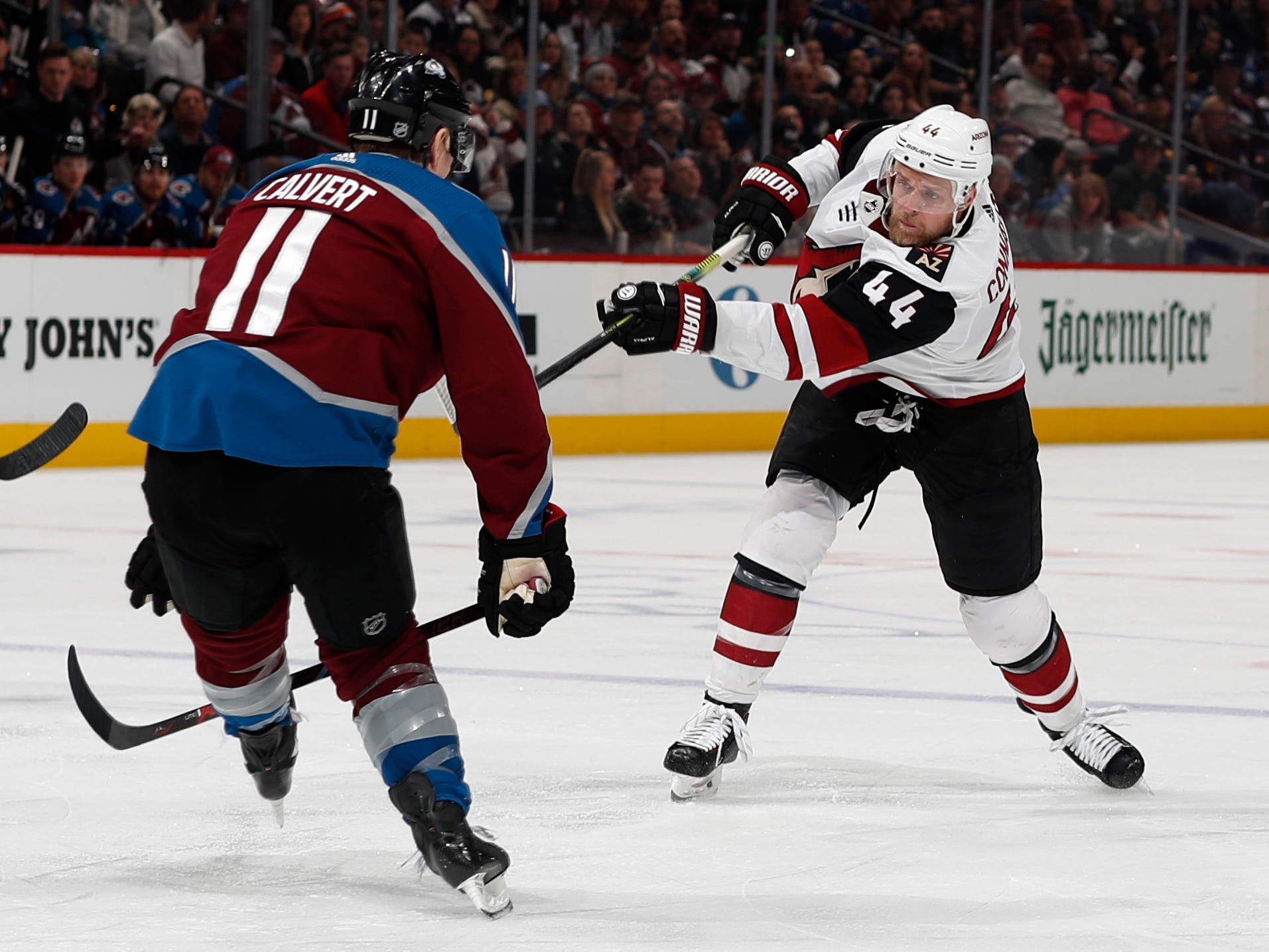 Arizona Coyotes defenseman Kevin Connauton, right, shoots the puck past Colorado Avalanche left wing Matt Calvert in the second period of an NHL hockey game Friday, March 29, 2019, in Denver.