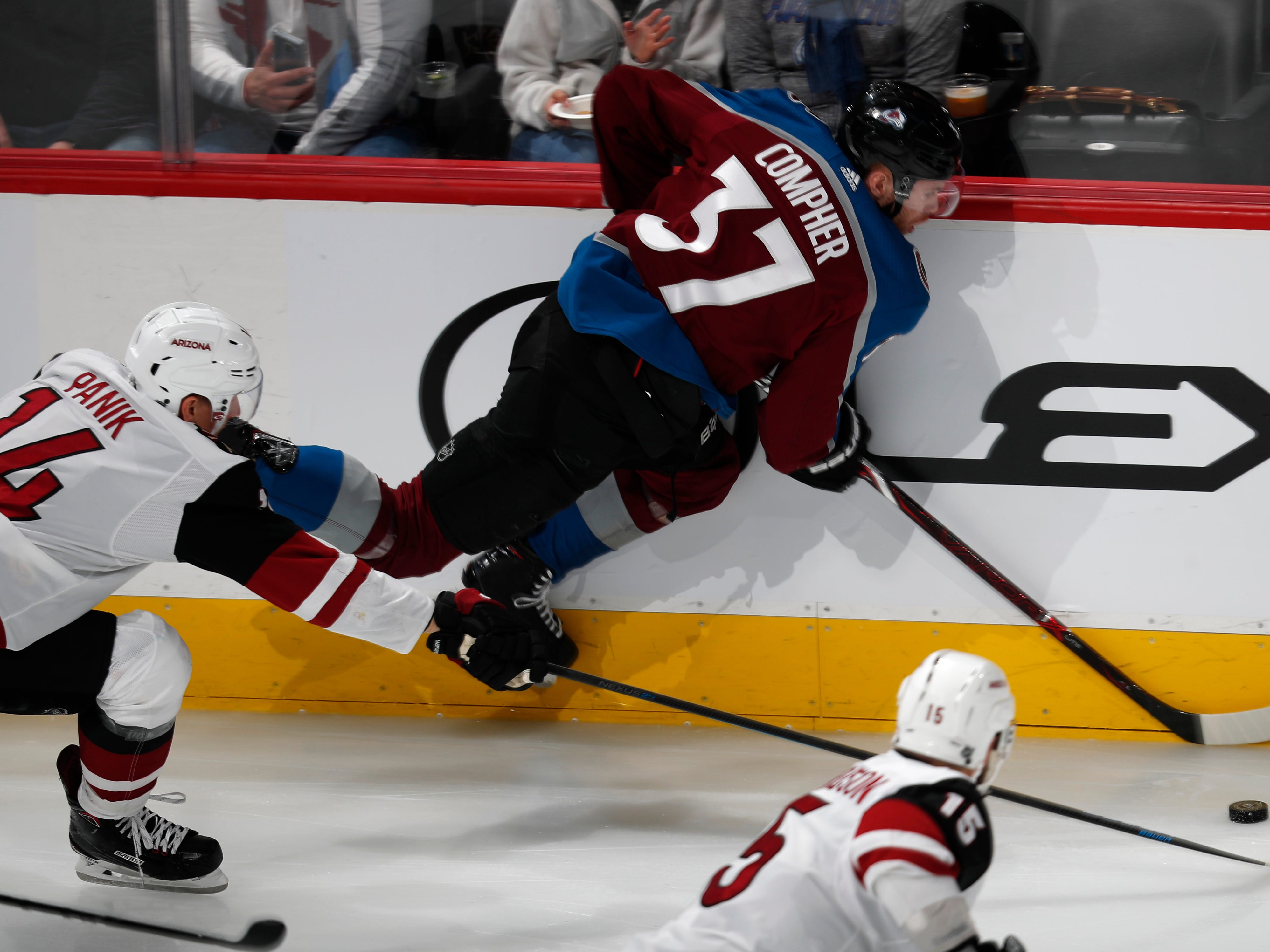 Colorado Avalanche left wing J.T. Compher, right, falls while pursuing the puck with Arizona Coyotes right wing Richard Panik in the first period of an NHL hockey game Friday, March 29, 2019, in Denver.