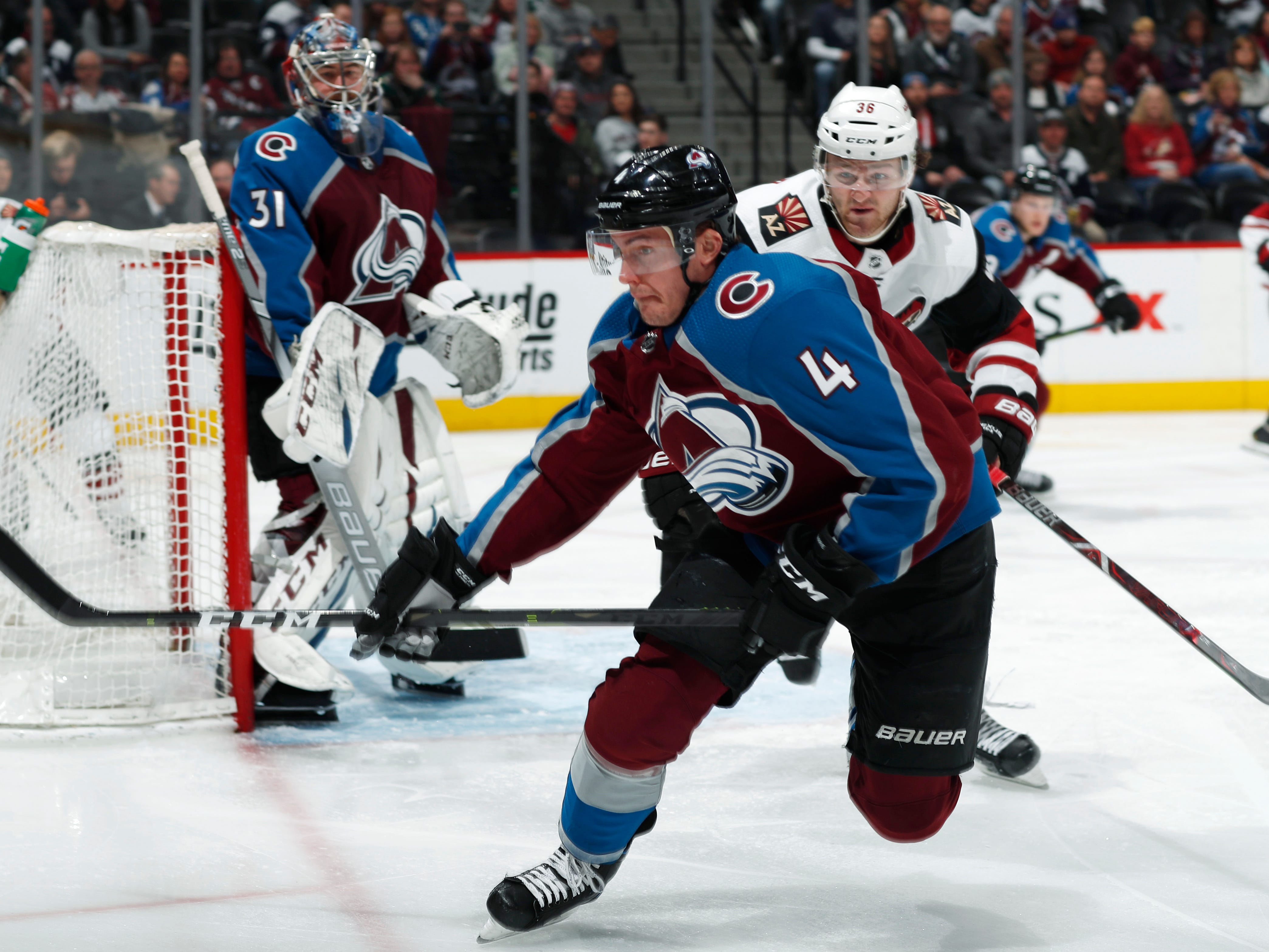 Colorado Avalanche defenseman Tyson Barrie, front, pursues the puck with Arizona Coyotes right wing Christian Fischer in the second period of an NHL hockey game Friday, March 29, 2019, in Denver.