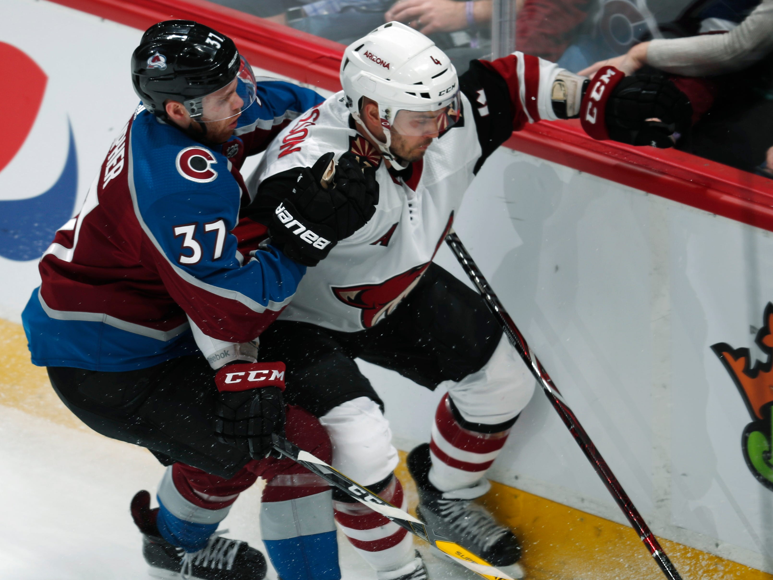 Colorado Avalanche left wing J.T. Compher, left, fights with Arizona Coyotes defenseman Niklas Hjalmarsson for control of the puck in the first period of an NHL hockey game Friday, March 29, 2019, in Denver.