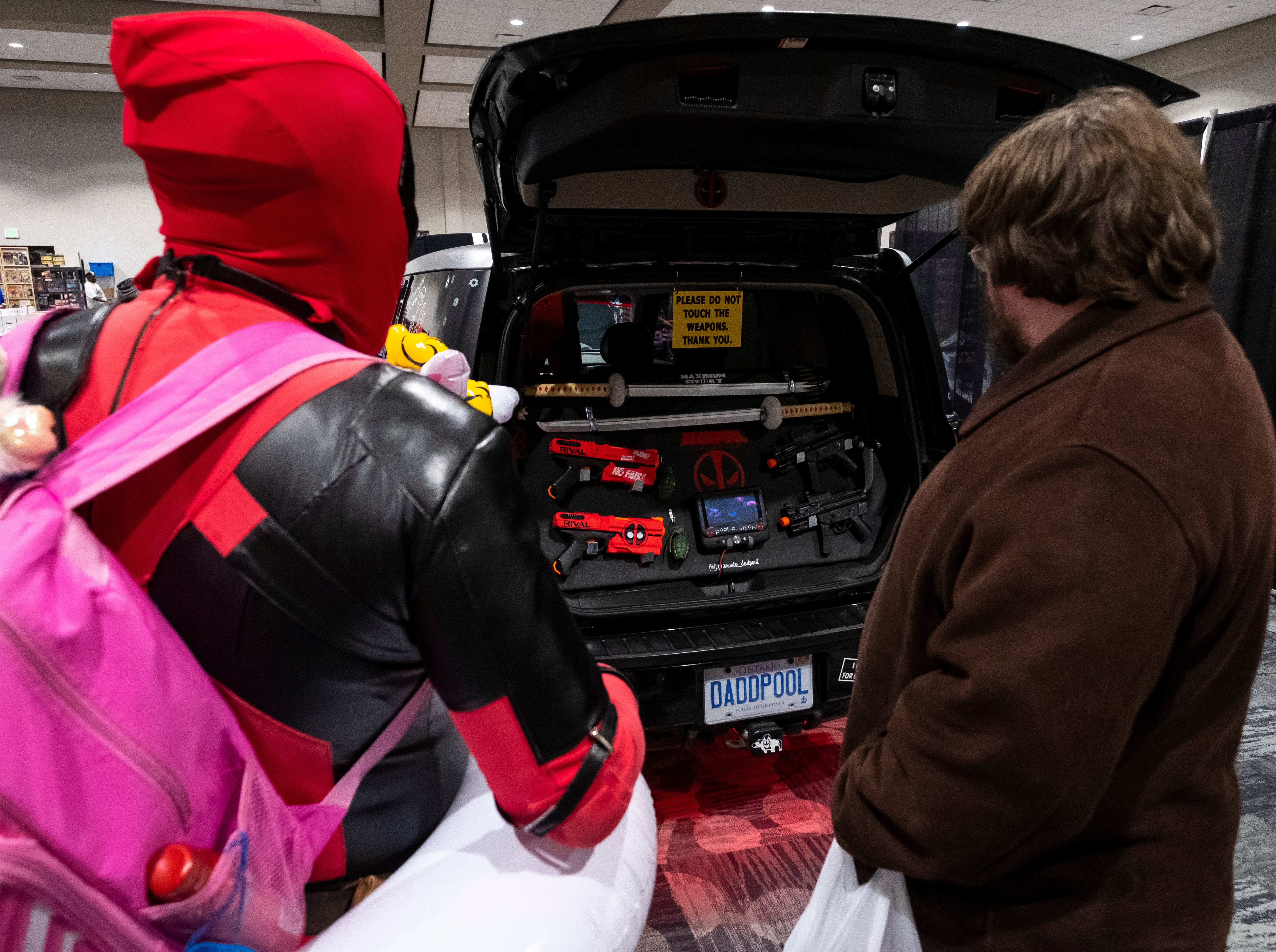 Trevor Lyn, left, also known as the Toronto Dadpool, talks about a slew of fake Deadpool-themed weapons mounted in the back of the Deadpoolmobile with Edward Gibson, of St. Clair, during Blue Water International Comic-Con Saturday, March 30, 2019 at the Blue Water Convention Center.