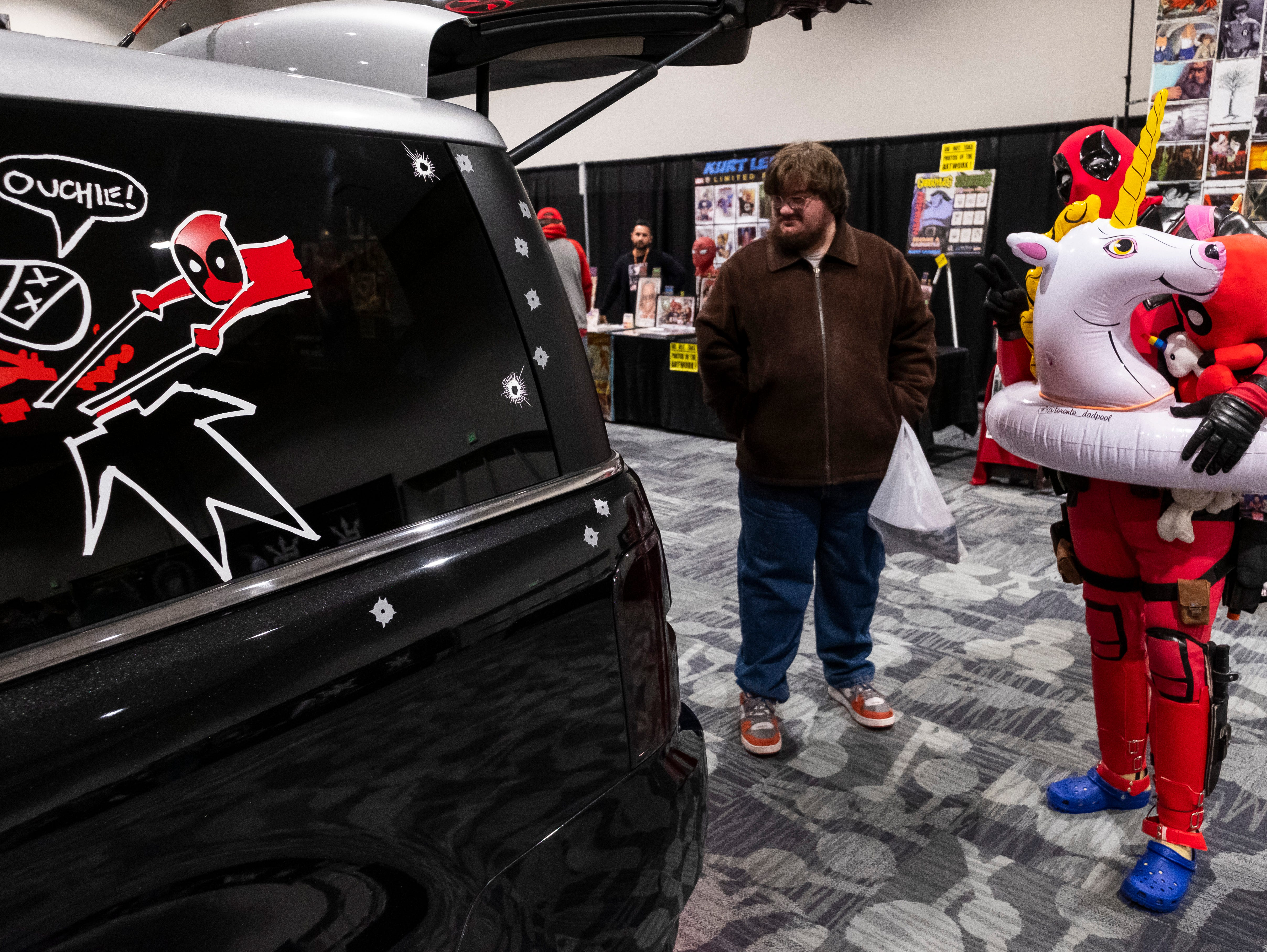 Trevor Lyn, also known as the Toronto Dadpool, right, strikes a pose while Edward Gibson, of St. Clair, admires the Dadpoolmobile Saturday, March 30, 2019 during Blue Water International Comic-Con.