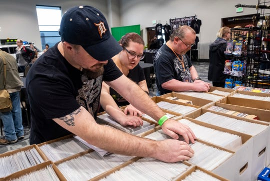 """After consulting a list of comic books they're hunting, Mark McCombs, left, or Port Huron, and Stephanie Harrod, center, of Davison, begin searchng through boxes full of different comics Saturday, March 30, 2019 during Blue Water International Comic-Con. """"I'm addicted to dollar comics,"""" said McCombs. """"I own too many."""""""