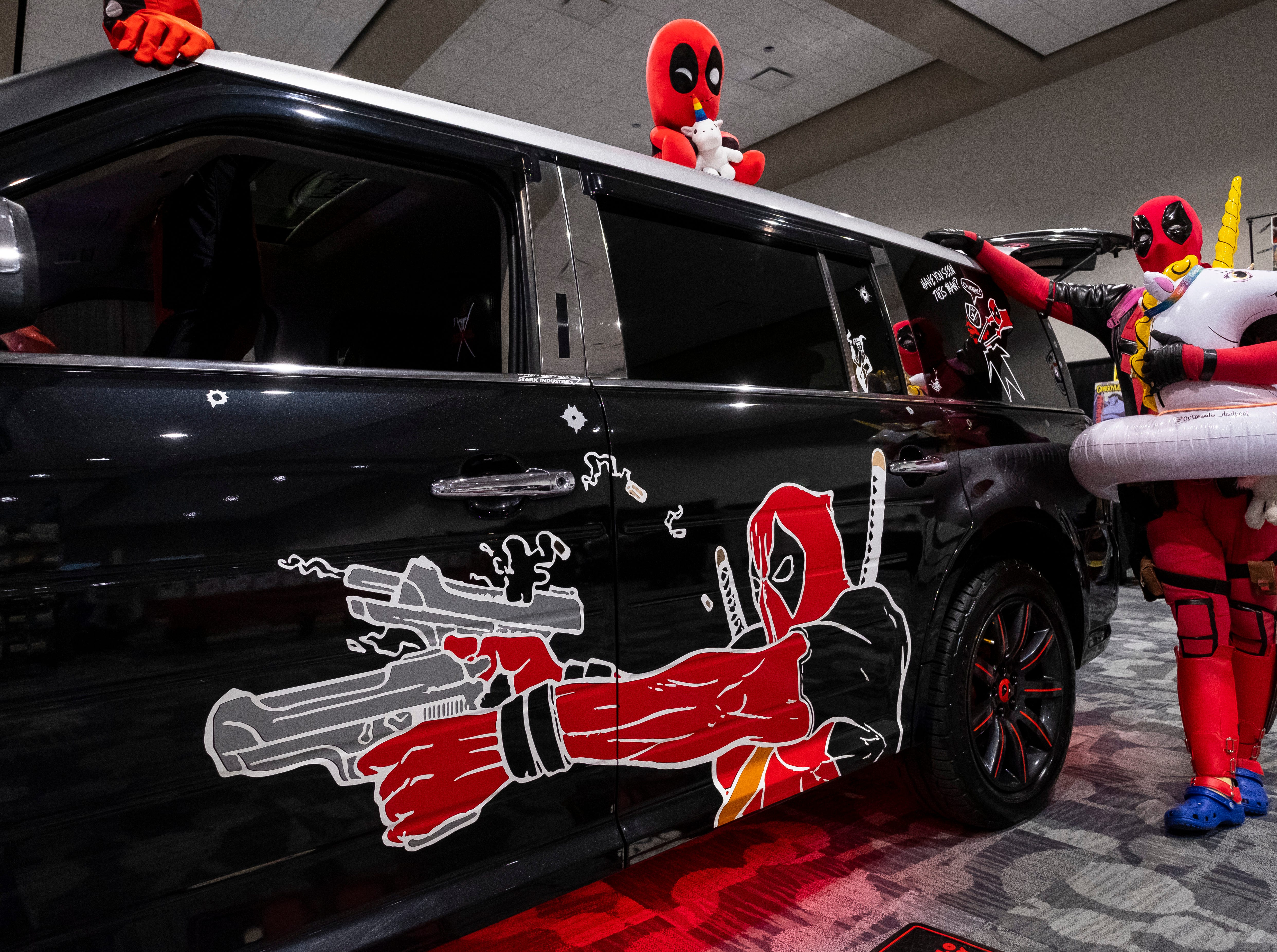 """Trevor Lyn, also known as the Toronto Dadpool, leans against the Dadpoolmobile while dressed as one of his variants of Deadpool Saturday, March 30, 2019 during Blue Water International Comic-Con. Lyn says he began cosplaying as Deadpool after visiting Toronto Comic Con with his son in 2016, where he met a man dressed as Deadpool. """"He was sitting on the floor drawing like Deadpool does, with crayons and paper, and (my son) sat with the guy … I just watched, and I saw the people coming up, getting pictures with them, and it looked like a lot of fun, so I just said I want to do it."""""""