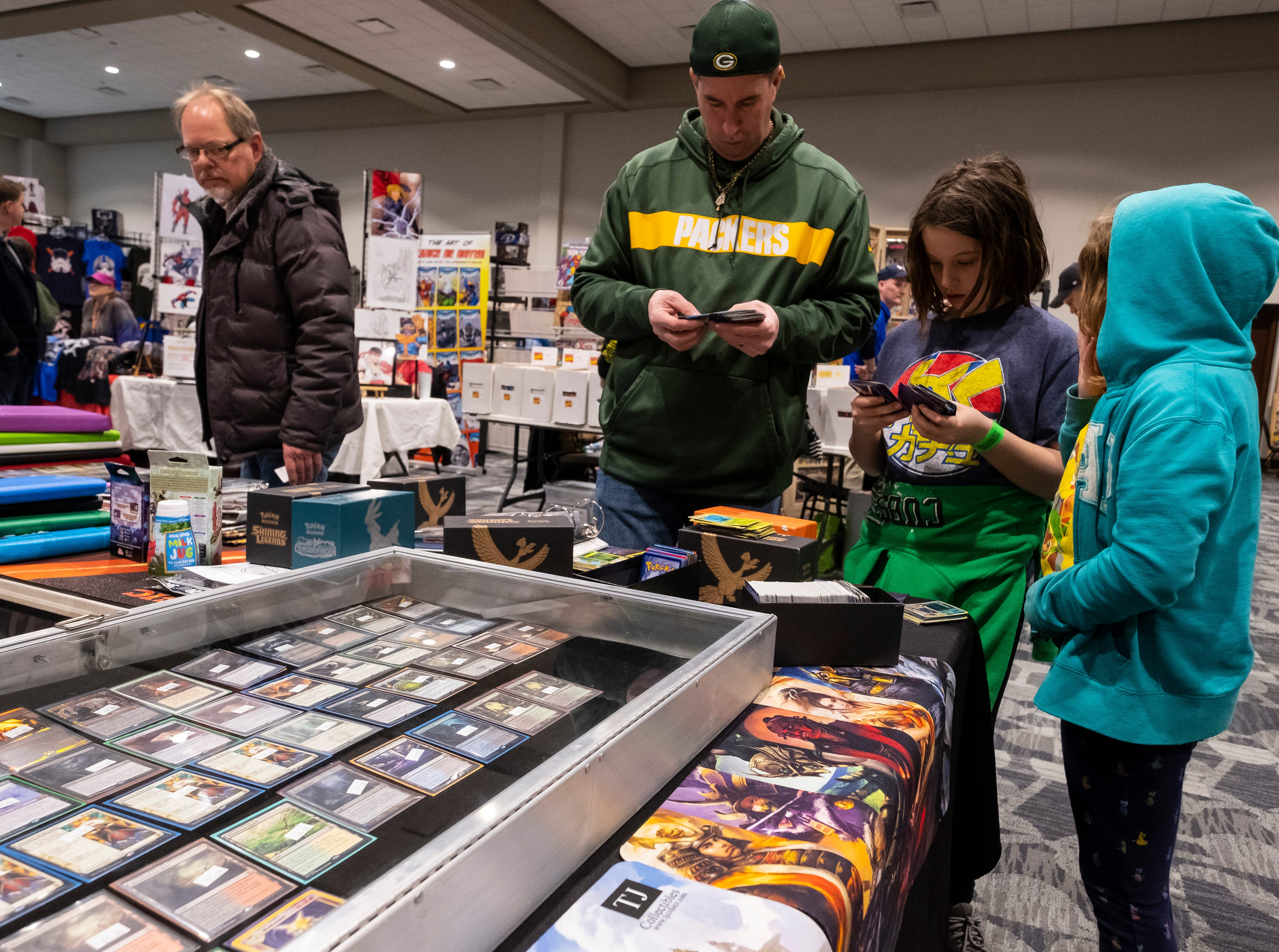 Kevin Meyers browses Pokemon cards with his daughters Keira, 9, center and Kayleigh, 8, right, at one of the vendors during Blue Water International Comic-Con Saturday, March 30, 2019 at the Blue Water Convnetion Center. Several of the vendors working the booth said most of their customers are families looking at different Pokemon and Magic: The Gathering cards.