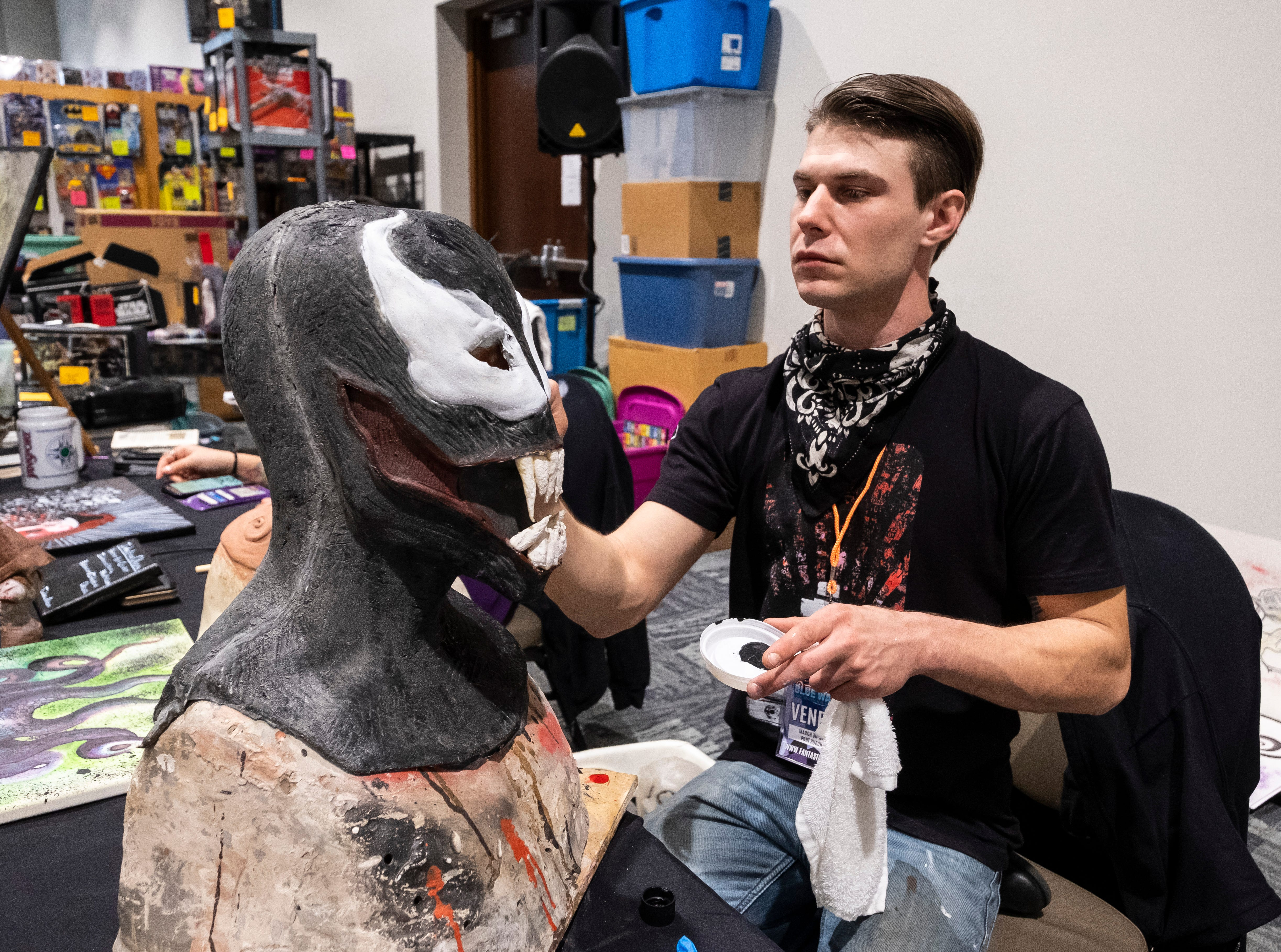Mike Parrent, owner of Industrious Obscura, paints a Venom mask Saturday, March 30, 2019 at his booth at Blue Water International Comic-Con at the Blue Water Convention Center. Parrent says by the end of the weekend, he will have several masks completed that will be for sale at his booth.