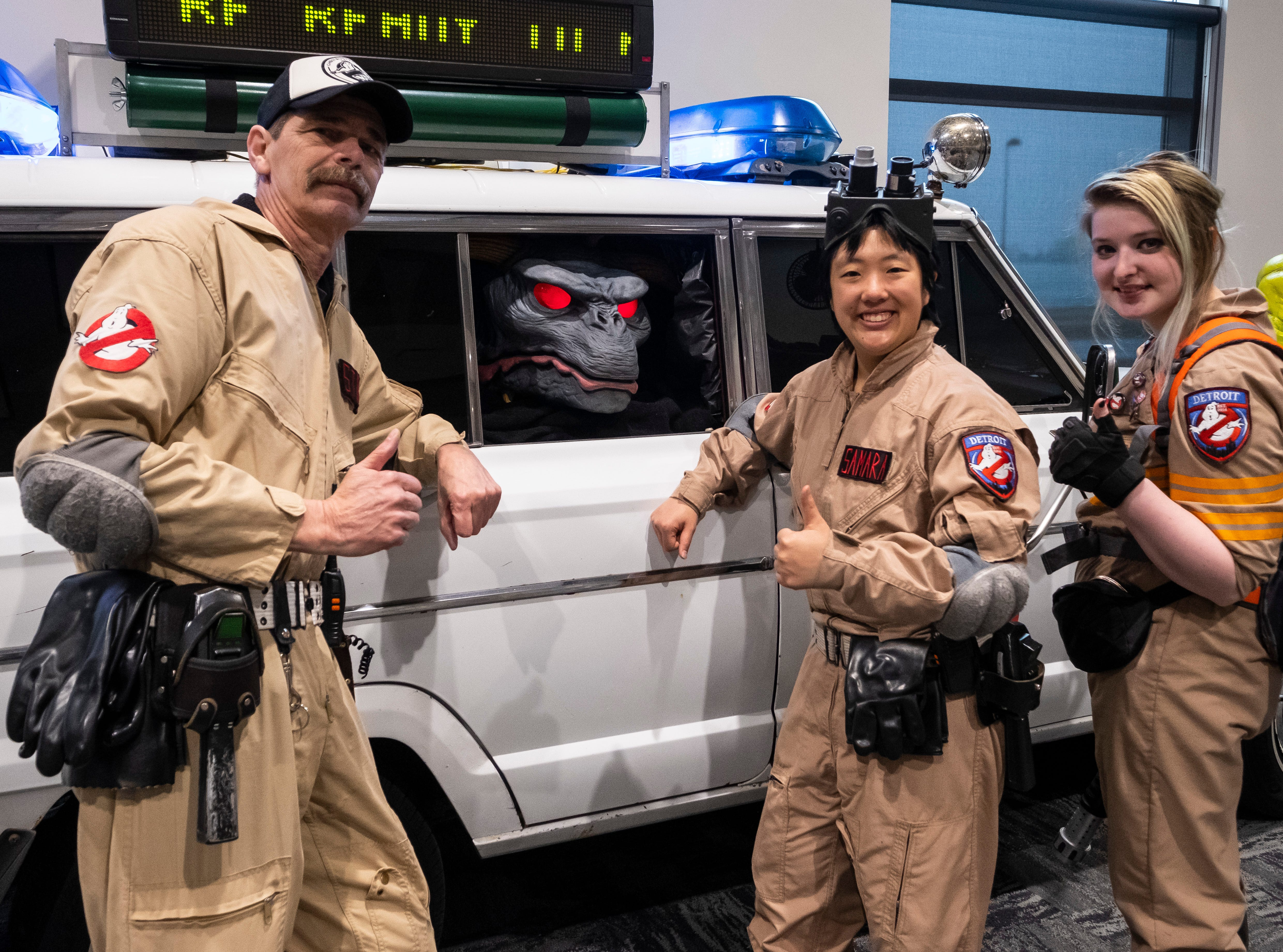 Detroit Ghostbusters Stan Lindow, left, Samara Shaw, center and Lauren Marquardt pose next to their vehicle Saturday, March 30, 2019 during Blue Water International Comic-Con.