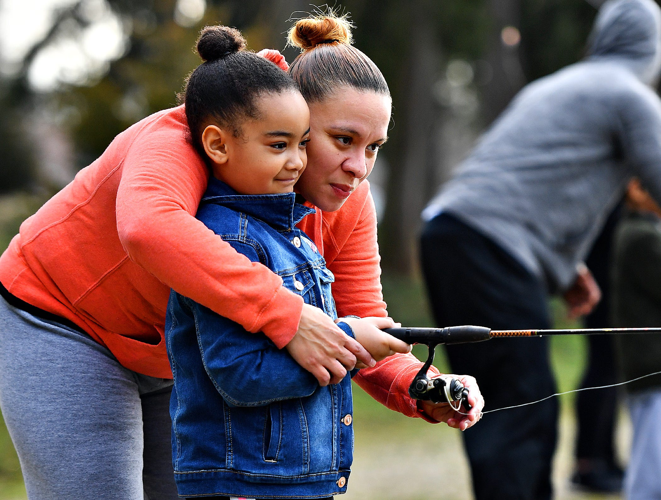 Nancy Moore, back, wraps her arms around her daughter Trinity, 6, as she helps to secure the fishing line during the 21st Annual William Shaffer Trout Fishing Derby at Kiwanis Lake in York City, Saturday, March 30, 2019. Dawn J. Sagert photo