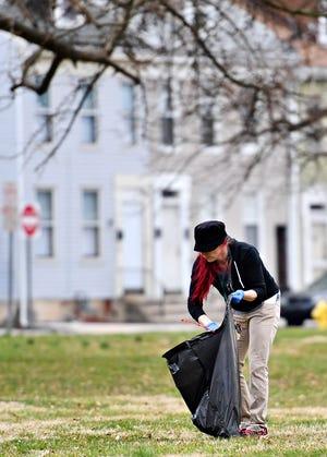 Parent Liaison Destiney Boldizar gathers trash into a garbage bag as Edgar Fahs Smith STEAM Academy begins their Spring Neighborhood Clean-up at Penn Park in York City, Saturday, March 30, 2019. Dawn J. Sagert photo
