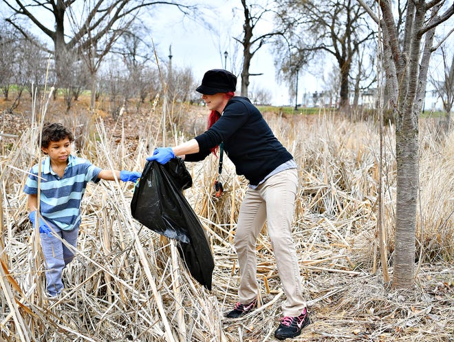 Parent liaison Destiney Boldizar, right, holds a bag out so her son, Dylan Boldizar, 8, can place trash in it as Edgar Fahs Smith STEAM Academy begins its Spring Neighborhood Cleanup at Penn Park in York City, Saturday, March 30, 2019. Dawn J. Sagert photo