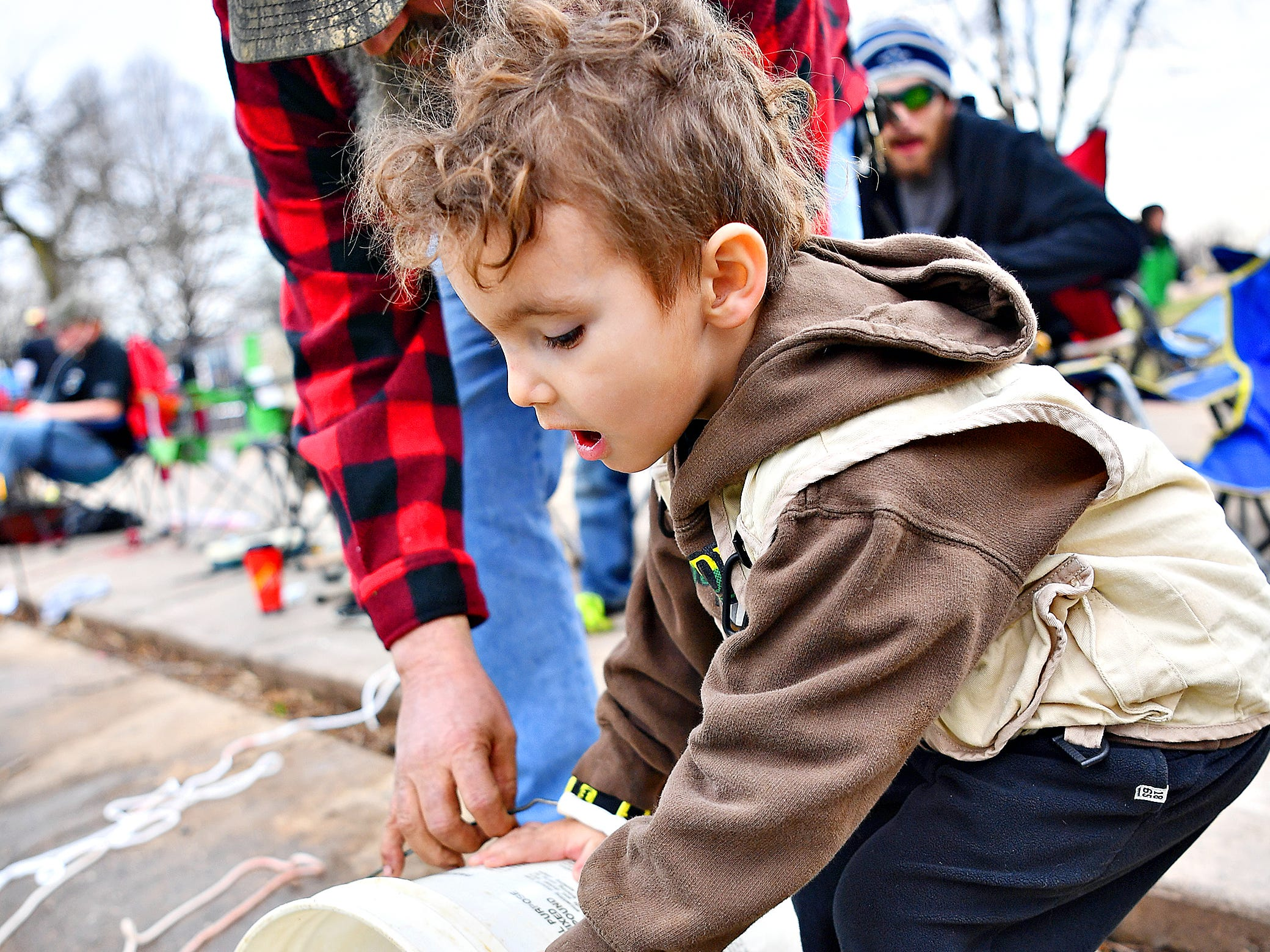 Mark Singleton Sr., left, of Dover, helps his grandson Matthew Singleton, 4,  of West Manchester Township, to pour a bucket of fish into Kiwanis Lake during the 21st Annual William Shaffer Trout Fishing Derby in York City, Saturday, March 30, 2019. Dawn J. Sagert photo
