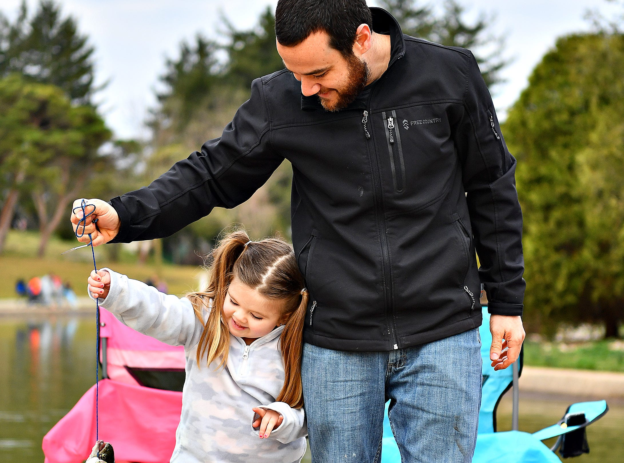 Daniel Bowen, right, of Spring Garden Township, and his daughter Charley Smith 4, carry the fish that they caught during the 21st Annual William Shaffer Trout Fishing Derby at Kiwanis Lake in York City, Saturday, March 30, 2019. Dawn J. Sagert photo