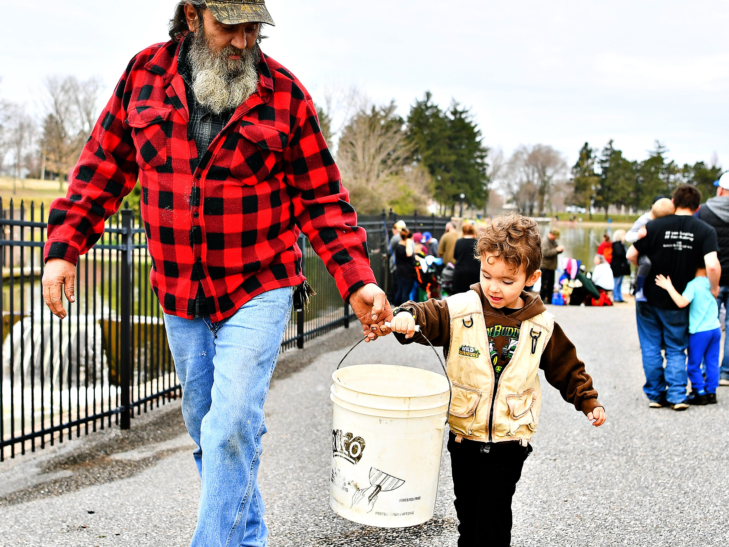 Mark Singleton Sr., left, of Dover, helps his grandson Matthew Singleton, 4,  of West Manchester Township, as they carry a bucket of fish to restock during the 21st Annual William Shaffer Trout Fishing Derby at Kiwanis Lake in York City, Saturday, March 30, 2019. Dawn J. Sagert photo