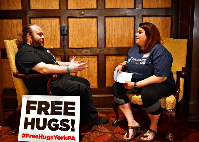 """John Beck, left, of York City, discusses his book title Free Hugs! with volunteer and Emily Ferber-Smith, of Hanover, as """"readers"""" interact with a library collection of human """"books"""" during the third Human Library: York event at York College Center for Community Engagement in York City, Saturday, March 30, 2019. Dawn J. Sagert photo"""