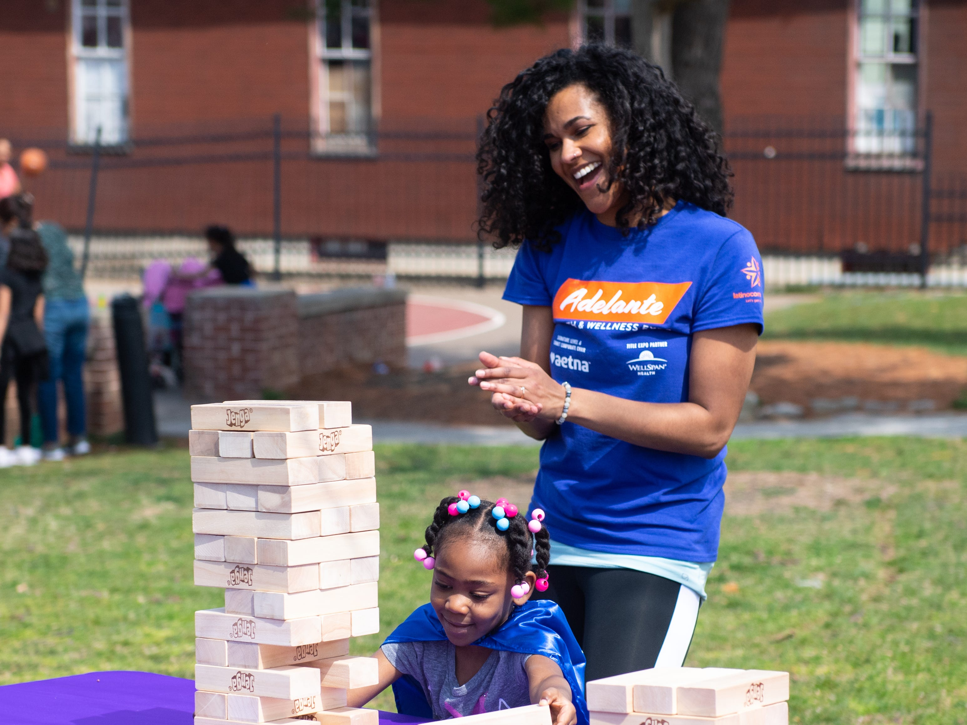 Zaria Pettigen carefully removes a block from the Jenga tower as Michelle Connett-Bernstein cheers her on during, March 30, 2019.