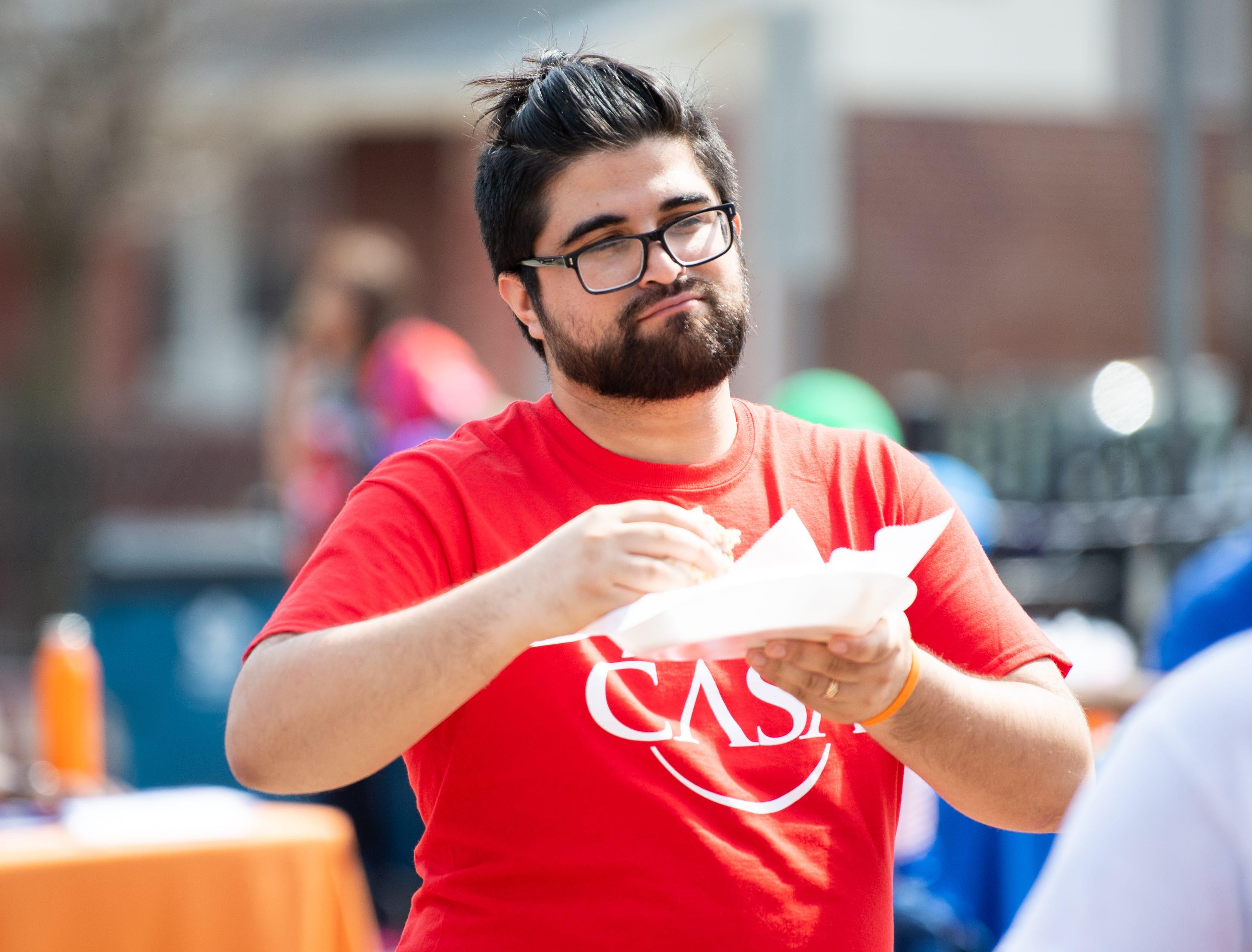 Earvin Gonzalez enjoys a burrito during the Adelante Festival at Renaissance Park, March 30, 2019.