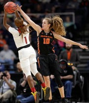 Oregon State guard Katie McWilliams (10) defends against Louisville guard Dana Evans (1) as Evans shoots for three points during the first half of a regional semifinal game in the NCAA women's college basketball tournament, Friday, March 29, 2019, in Albany, N.Y. (AP Photo/Kathy Willens)