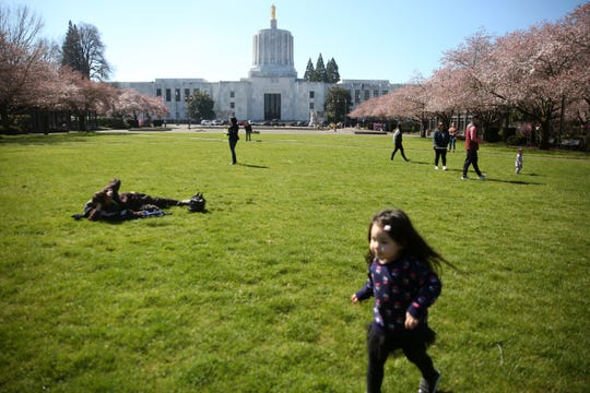 People gather as cherry blossom trees begin to bloom near the Oregon State Capitol in Salem on March 30, 2019.