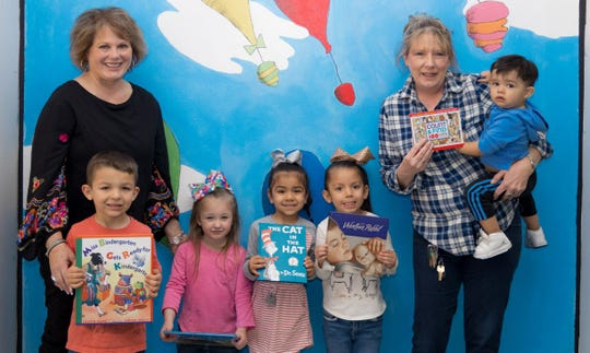 Christy Vanoss, left, representing San Angelo Retired Teachers & Associates presents books to Cynthia Lackey, director of the Early Childhood Center. The Children's Book Project is a service activity that puts books in the hands of children who may otherwise not have books of their own.