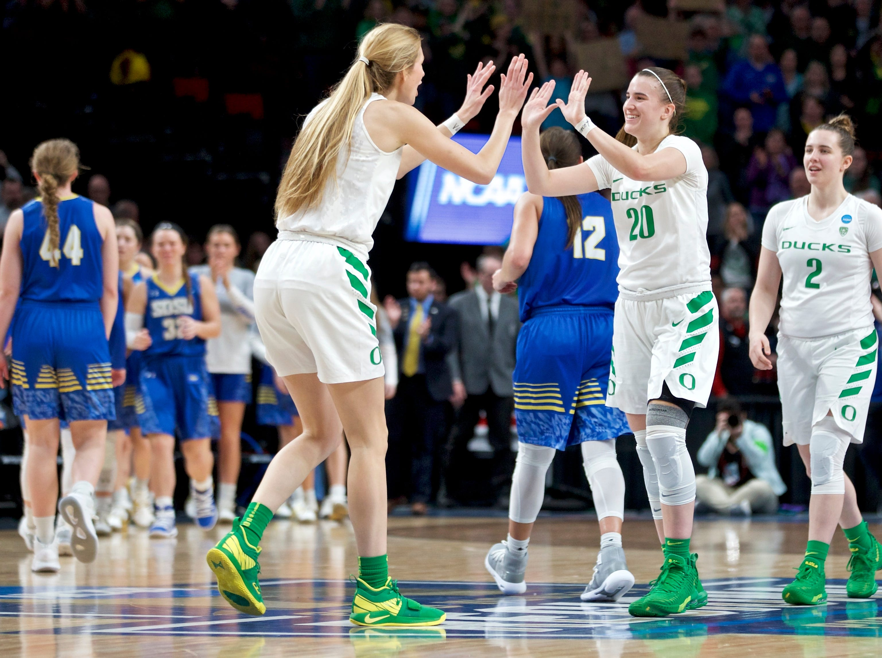 Oregon guard Sabrina Ionescu (20) and forward Lydia Giomi high-five at the end of the team's regional semifinal against South Dakota State in the NCAA women's college basketball tournament Friday, March 29, 2019, in Portland, Ore. Oregon won 63-53. (AP Photo/Craig Mitchelldyer)