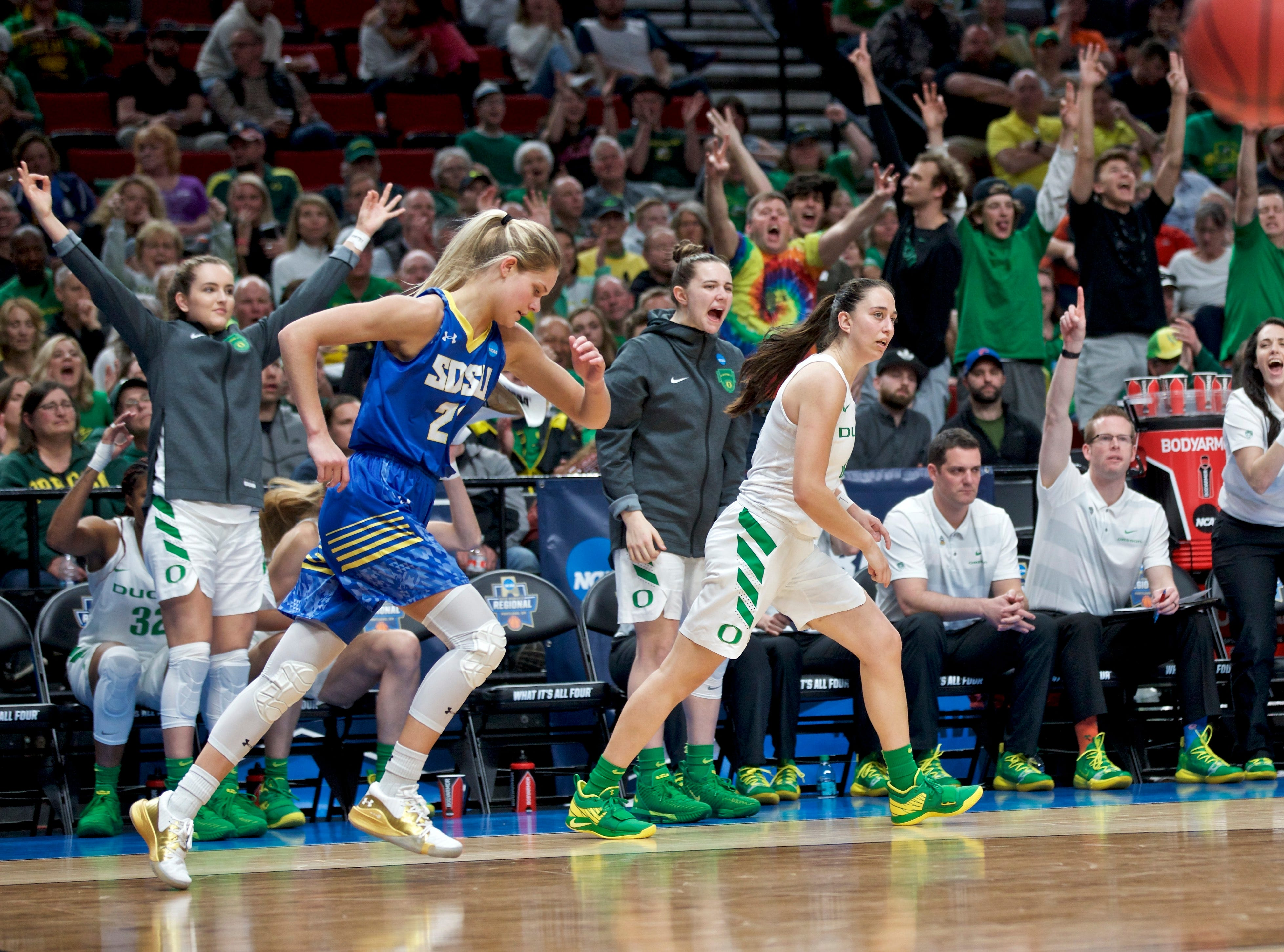 Oregon guard Taylor Chavez, left, and guard Morgan Yaeger, second from right, react after guard Maite Cazorla made a 3-point basket over South Dakota State guard Tylee Irwin, front left, during the second half of a regional semifinal in the NCAA women's college basketball tournament Friday, March 29, 2019, in Portland, Ore. Oregon won 63-53. (AP Photo/Craig Mitchelldyer)