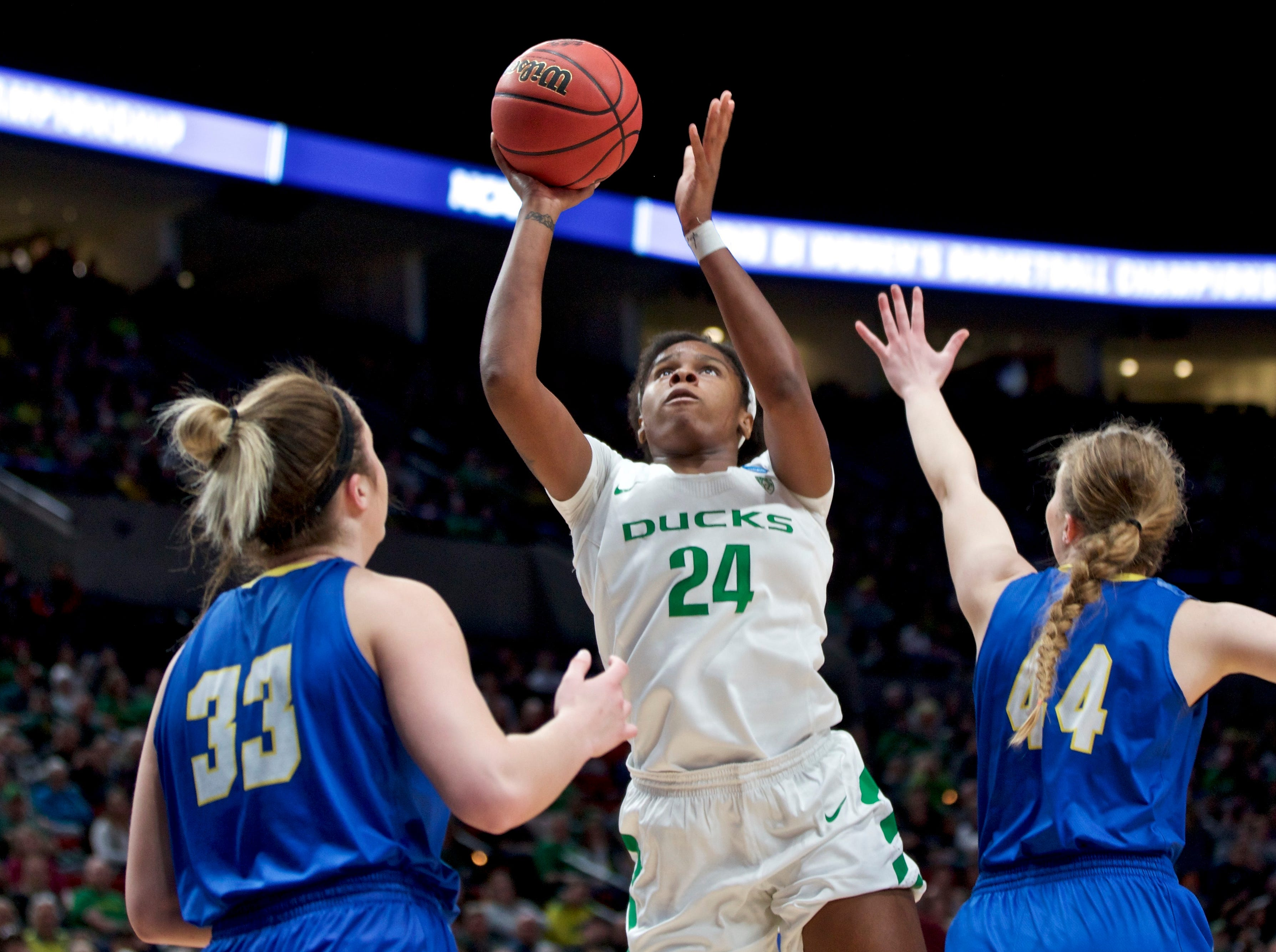 Oregon forward Ruthy Hebard, center, shoots in front of South Dakota State forwards Paiton Burckhard, right, and Myah Selland during the first half of a regional semifinal in the NCAA women's college basketball tournament Friday, March 29, 2019, in Portland, Ore. (AP Photo/Craig Mitchelldyer)