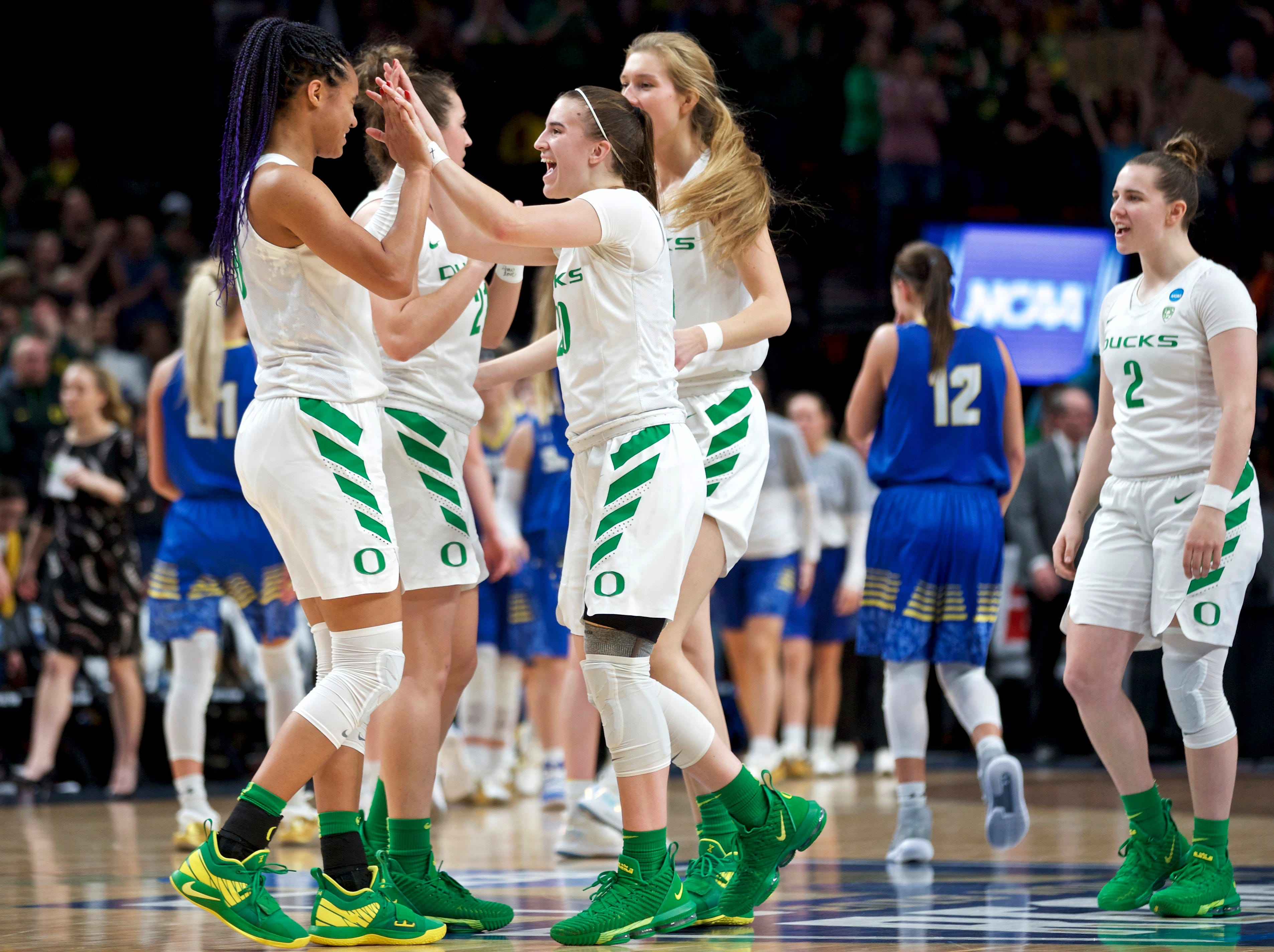 Oregon guard Sabrina Ionescu, center, high-fives forward Satou Sabally, left, at the end of a regional semifinal against South Dakota State in the NCAA women's college basketball tournament Friday, March 29, 2019, in Portland, Ore. Oregon won 63-53. (AP Photo/Craig Mitchelldyer)