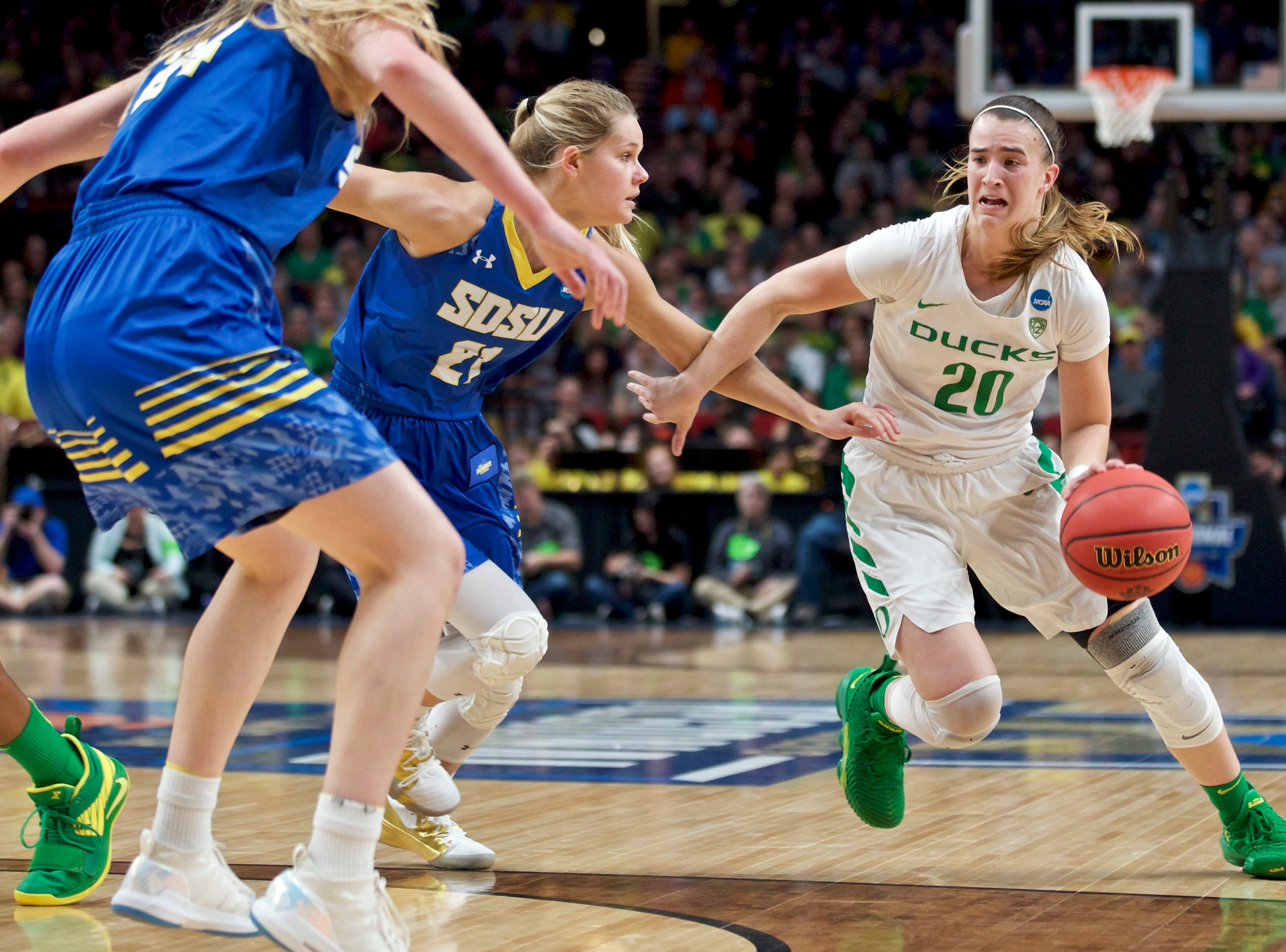 Oregon guard Sabrina Ionescu, right, drives to the basket past South Dakota State guard Tylee Irwin during the first half of a regional semifinal in the NCAA women's college basketball tournament Friday, March 29, 2019, in Portland, Ore. (AP Photo/Craig Mitchelldyer)