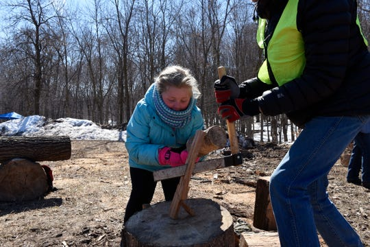 Annemarie Mulrooney, 7, of Inver Grove Heights, makes kindling with the help of a volunteer at the St. John's Maple Syrup Festival Saturday, March 30, in Collegeville.