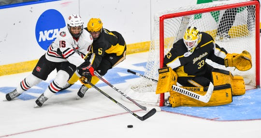 Micah Miller of St. Cloud State works against Ryan Polin  of American International College in front of goaltender Zackarias Skog during the second period of the NCAA west region semifinal game Friday, March 29, at Scheels Arena in Fargo, ND.