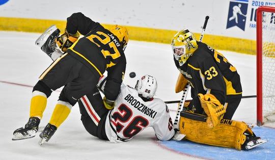 Easton Brodzinski tries to get a shot on American International College goaltender Zackarias Skog  during the third period of the NCAA west region semifinal game Friday, March 29, at Scheels Arena in Fargo, ND.