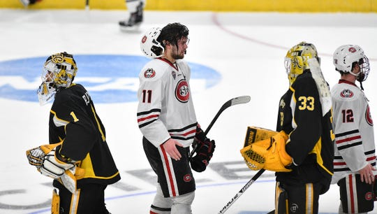 Ryan Poehing of St. Cloud State and shares handshakes with  American International College players  following  the NCAA west region semifinal game Friday, March 29, at Scheels Arena in Fargo, ND.