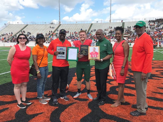 AP All-American punter Chris Faddoul (center) is honored with awards for athletics and academics during halftime of the Orange & Green Game on Saturday, March 30, 2019. From L-R: Kendra Green (compliance director) Dr. Genyne Boston (deputy athletics director) Willie Simmons (football head coach), Dr. Larry Robinson (FAMU president), Sharon Robinson and Dr. John Eason (athletics director).