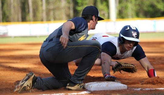Wakulla Christian's Allen Willis dives back into first on a pick-off attempt but is called out on a tag by Aucilla Christian first baseman Blake Wirick as the host Saints beat the Warriors 6-2 on Friday, March 29, 2019.