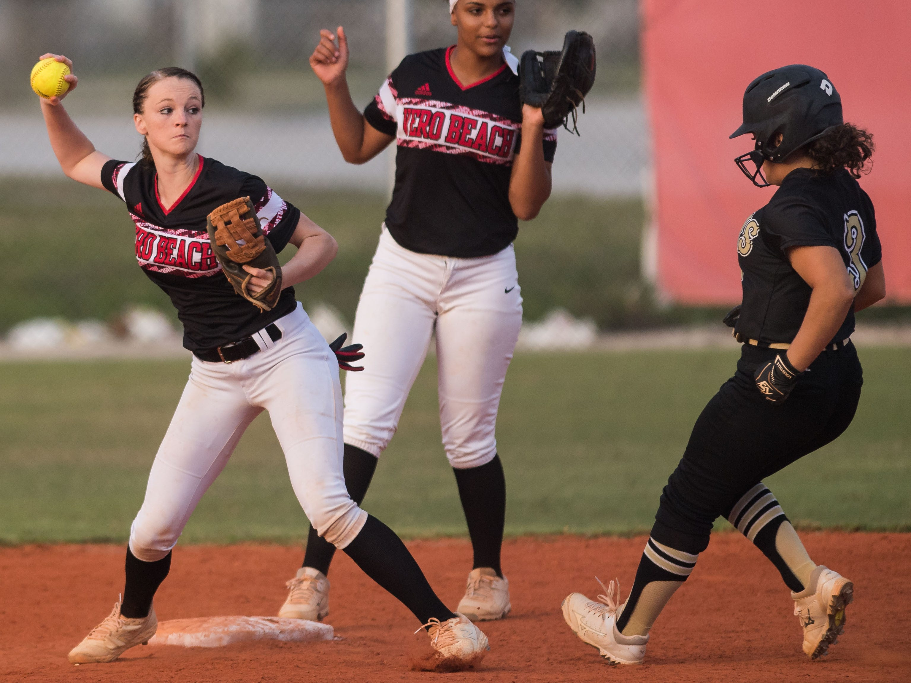 Vero Beach shortstop Summer Washburn (left) forces Treasure Coast's Amanda Ruiz out at second and throws to first for a double play during the second inning of the high school softball game Friday, March 29, 2019, at Vero Beach High School.