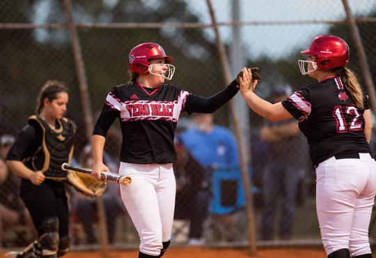 Vero Beach's Shayne Hewitt (left) is congratulated by teammate Kirsten Pulvermacher after being hit in to score on a double by Abigail Hofer against Treasure Coast during the third inning of the high school softball game Friday, March 29, 2019, at Vero Beach High School.