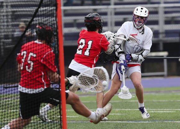 John Jay's Bryce Ford (9) fires a shot that is stooped by Rye goalie Emmet Carroll (35) during boys lacrosse action at John Jay High School in Cross River March 29, 2019. John Jay won the game 8-6.