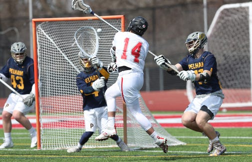 Somers' TJ Deagan (14) fires a shot on Pelham goalie Christian Morfit (4) during boys lacrosse action at Somers High School March 30, 2019. Somers won the game.