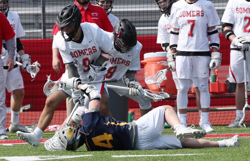 Somers' Nick Rossi (9) and Brandon LaSpina (8) battle for a loose ball with Pelham's Lance Brady (34) during boys lacrosse action at Somers High School March 30, 2019. Somers won the game.