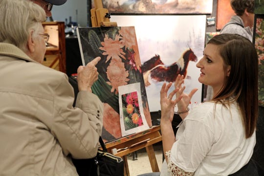 Lori Kirwin talks with visitors about using oil over watercolors at Cowboy True Saturday, March 30, 2019, at The Forum.