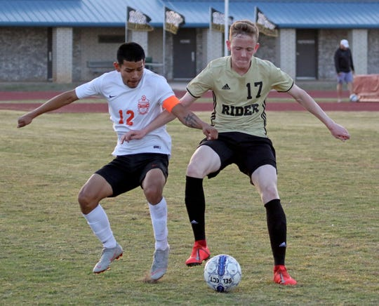 Rider's Jackson Redding (17) fights to keep the ball from Caprock's Andres Soria Friday, March 29, 2019, at Garnett Stadium.