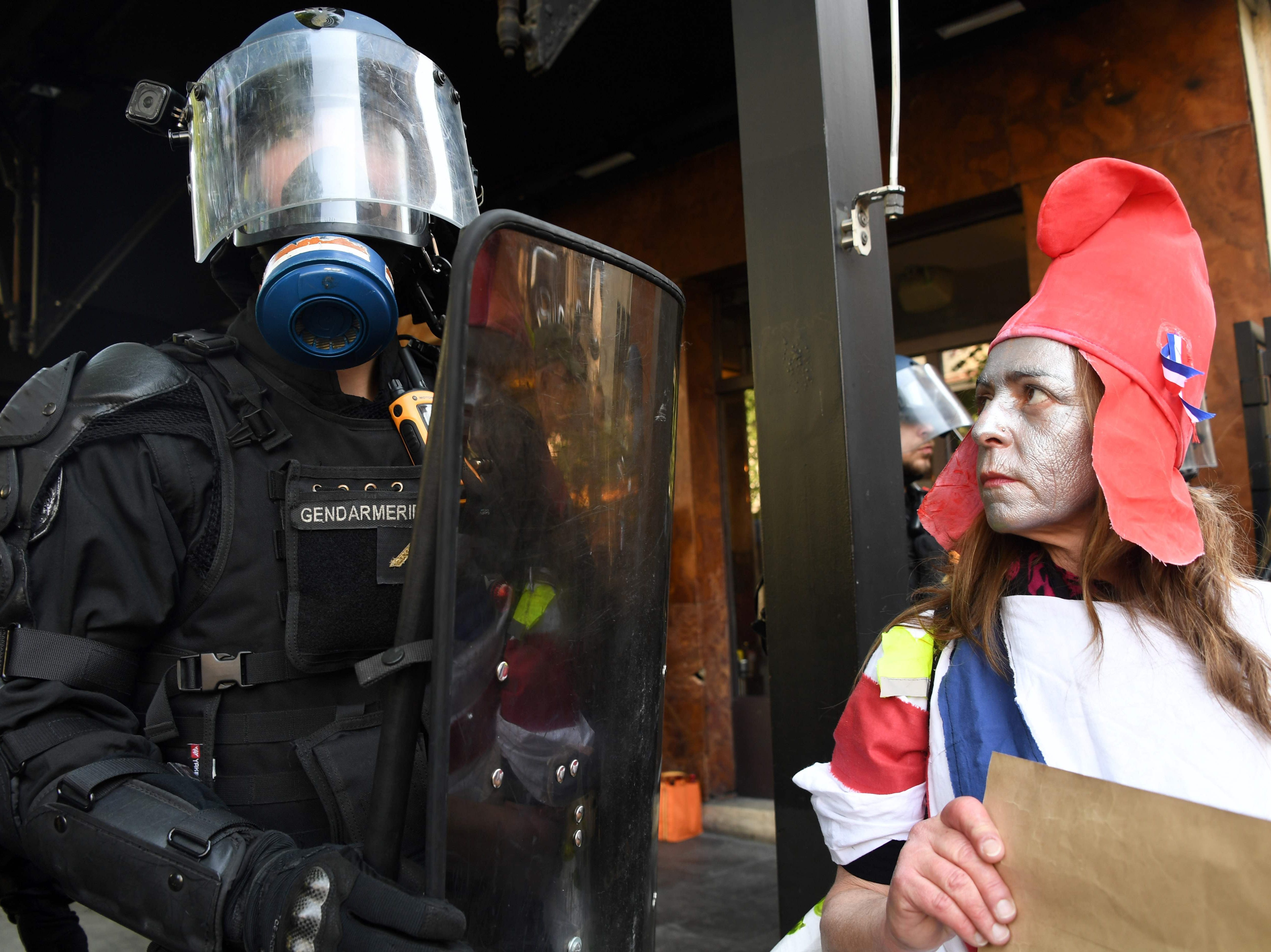 "A woman wearing make up and the Phrygian cap, referring to France's Marianne, looks at an anti-riot gendarme during a demonstration as part of a 20th consecutive saturday of protests called by the ""yellow vests"" (gilets jaunes) movement, on March 30, 2019, in Bordeaux, western France. The ""yellow vest"" movement - so-called after the protesters' high-visibility jackets - began nationwide five months ago over fuel taxes but quickly grew into a broader wave to protest against French President's policies and his top-down style of governing, high cost of living, government tax reforms and for more ""social and economic justice."""