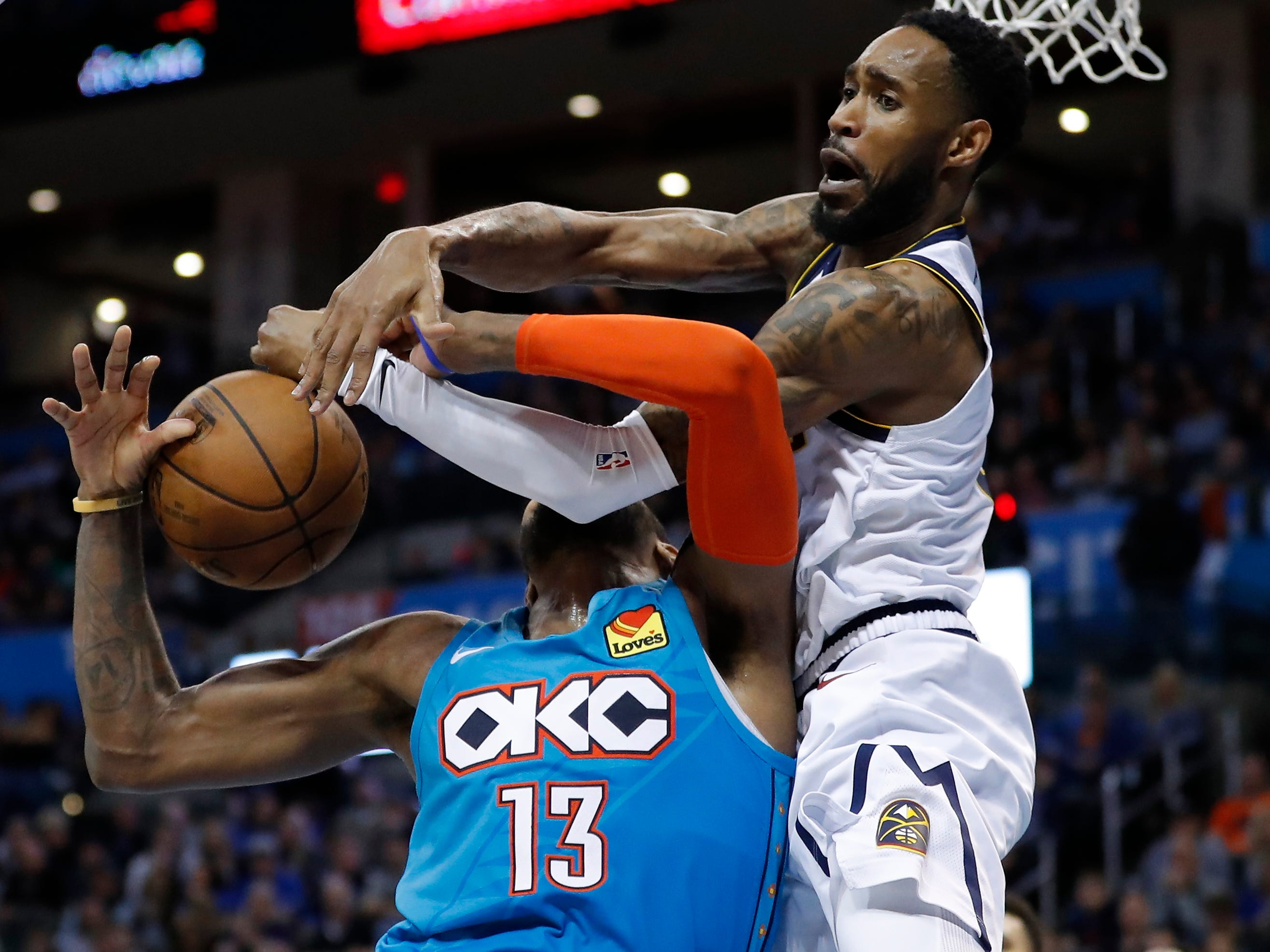 March 29: Nuggets defender Will Barton (5) fouls Thunder forward Paul George (13) on a second-half drive tho the basket in Oklahoma City.
