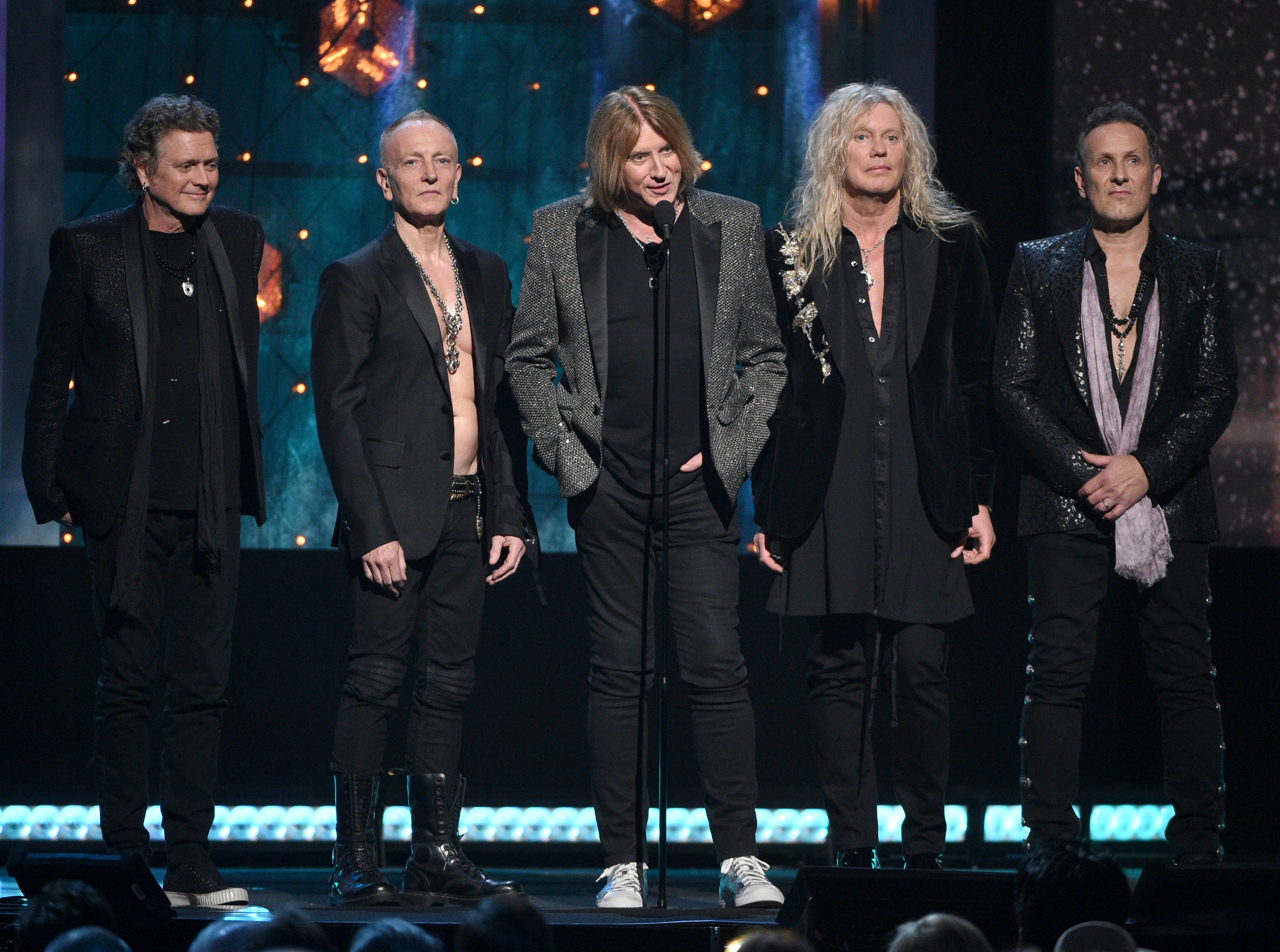 Def Leppard members Rick Allen, left, Phil Collen, Joe Elliott, Rick Savage and Vivian Campbell take the stage.